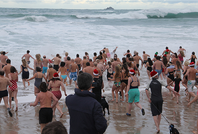 Crowds rush into the chilly waters