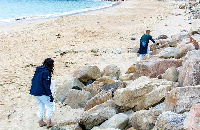 The Aspects Holidays team climbing over rocks looking for rubbish at Praa Sands beach.